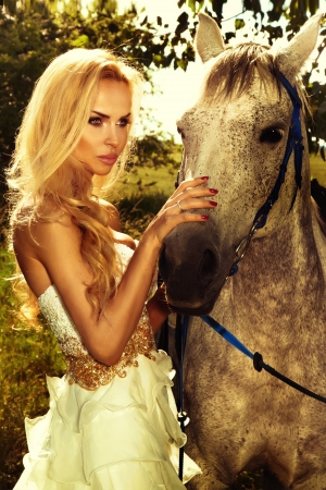 Close-up photo of attractive blonde woman posing with horse in the green garden.