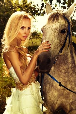 femme a cheval: Fermer-up photo de jeune femme blonde attirante posant avec cheval de dans le jardin vert.