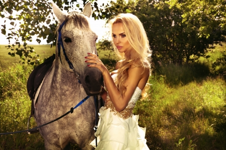 Photo of fashionable beautiful blonde woman posing with horse in green garden.  photo