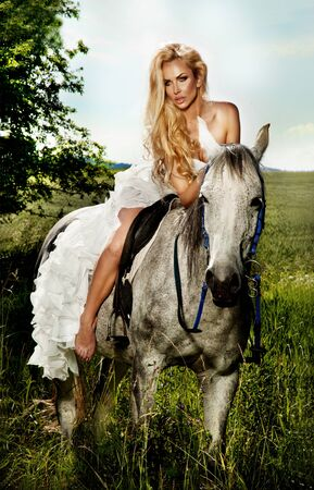 Beautiful young blonde woman sitting on a horse in white dress, in green garden. photo