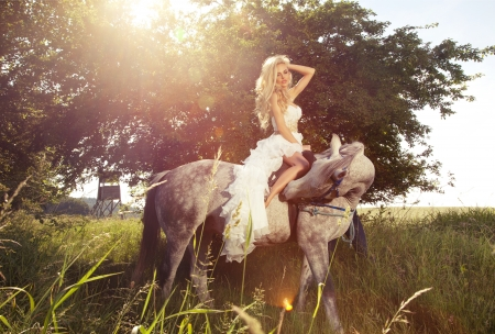 Attractive blonde woman riding a horse in sunny day wearing white dress in garden. Stock Photo