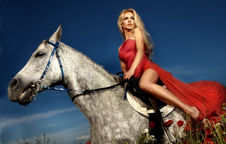 Fashionable blonde woman riding a horse in sunny day. Long curly hair.