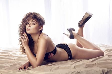 lenceria: Mujer atractiva con el pelo rizado largo acostado en la cama en ropa interior y zapatos de tacón alto, mirando a cámara.