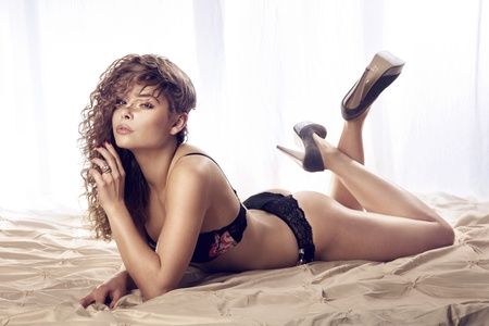 Sexy woman with long curly hair lying on bed in lingerie and high heels, looking at camera. Stock Photo