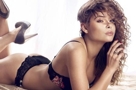 lenceria: Retrato de mujer joven y hermosa en ropa interior sensual en la cama, mirando la cámara. Foto de archivo