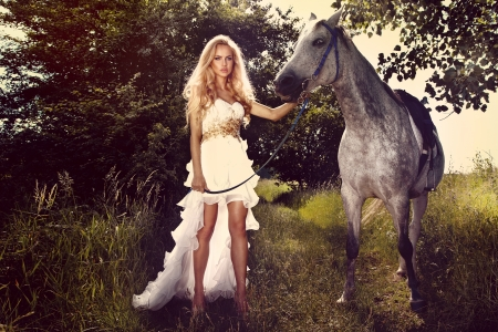 Beautiful young woman wearing fashionable white dress posing with horse in garden on sunny day.