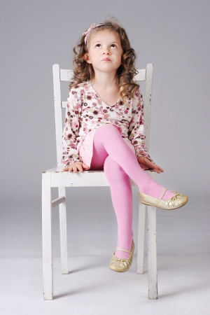 Cheerful little girl with curly long hair sitting on the white chair wearing pink clothes, making faces.
