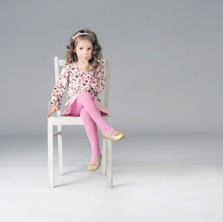 Fashionable thoughtful little girl posing on the white chair, looking away. Long curly hair. Pink clothes. photo