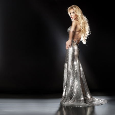 Beautiful young blonde woman posing in fashionable silver evening dress on the scene. Long curly hair. Elegant look.