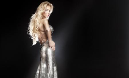 Atemberaubende junge schöne blonde Frau mit silbernen Abendkleid posiert und schaute weg. Langen lockigen Haar. Standard-Bild - 18872493