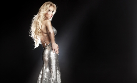 Stunning young beautiful blonde woman wearing silver evening dress posing, looking away. Long curly hair.  photo