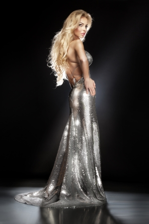 Fashionable of beautiful elegant young woman wearing a silver sequined evening dress with her hands on her hips. Healthy long blonde hair.