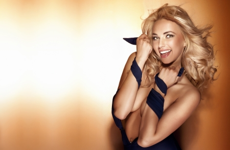 Beautiful happy smiling blonde woman posing, looking at camera. Long healthy hair.