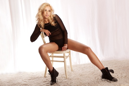 Fashionable photo of beautiful young sexy woman posing, sitting on chair, looking at camera. Stock Photo - 19061684