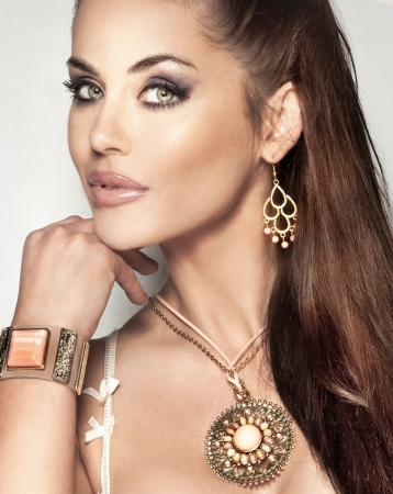 Portrait of fashionable beautiful woman with long brunette hair and amazing jewellery.