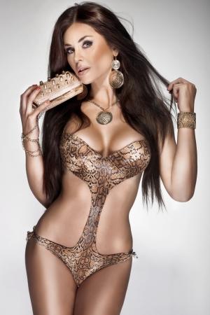 chica sexy: Mujer joven y atractiva morena con el pelo largo sano posando en traje de ba�o de moda. Una gran cantidad de joyas de oro. Perfecto cuerpo.