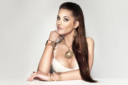 Fashionable beautiful brunette woman with a lot of jewelry, looking at camera. Long healthy hair. photo