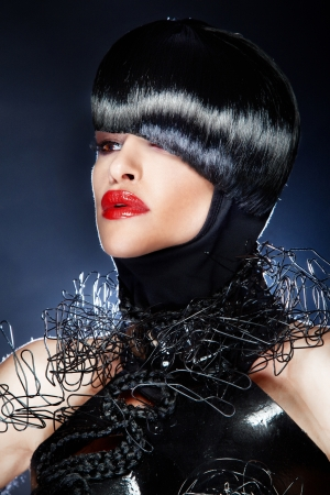 Fashionable portrait of beautiful woman with black hair, modern hairstyle, red lips and jewelry. photo