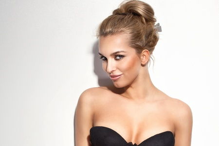 Portrait of cheerful blonde young woman smiling, looking at camera, wearing black bra. Banco de Imagens