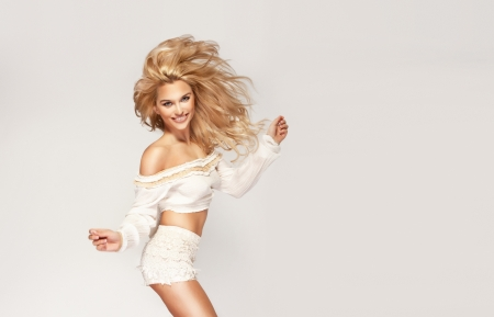 Fashionable young blonde woman jumping wearing white clothes. A lot of copyspace. photo