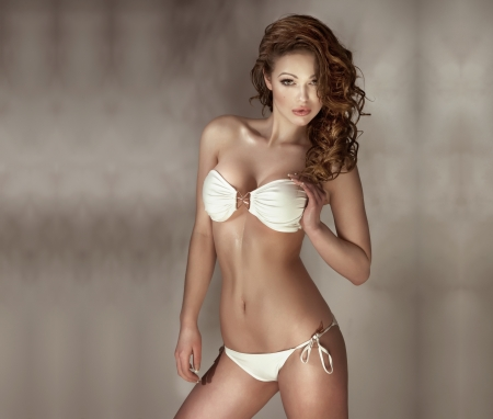 Sensual woman with perfect body wearing fashionable white swimwear posing