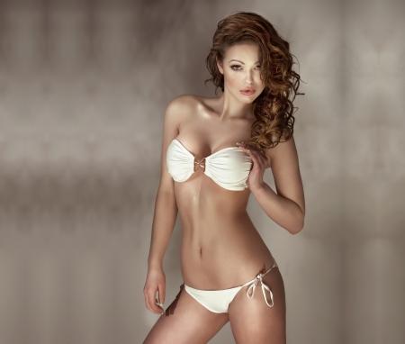 hot girl nude: Sensual woman with perfect body wearing fashionable white swimwear posing