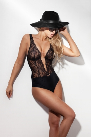 fashionable sexy blond woman wearing black hat, sunglasses and sensual lace lingerie. photo