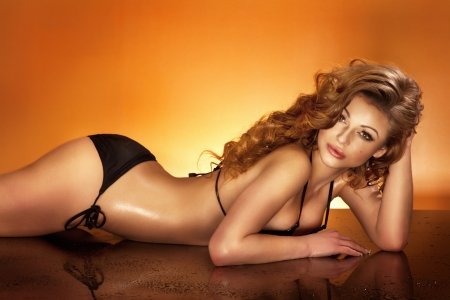 Attractive young woman relaxing, lying in black swimwear, looking at camera.