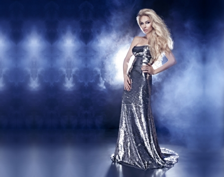 Beautiful young blonde woman posing in fashionable silver evening dress over the dark interior Standard-Bild