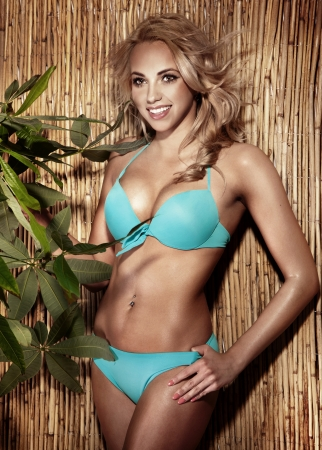 Photo of cheerful young blonde woman wearing blue bikini on sunny day. photo