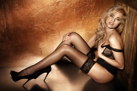 mujer desnuda sentada: Foto de la sensual mujer rubia sentada en el suelo en pose sexy, mirando a la c�mara.
