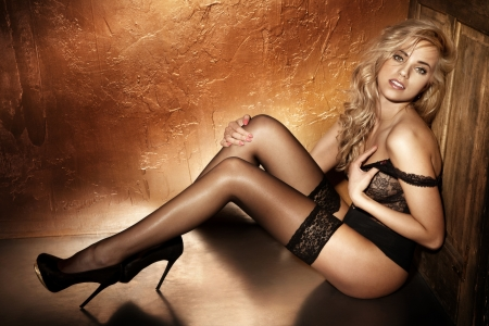 nude pretty girl: Photo of sensual blonde woman sitting on the floor in sexy pose, looking at camera.