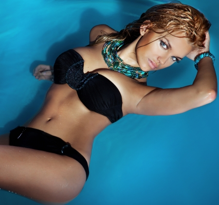young bikini: Portrait of beautiful young sensual woman posing in swimming pool wearing black swimsuit, looking at camera.