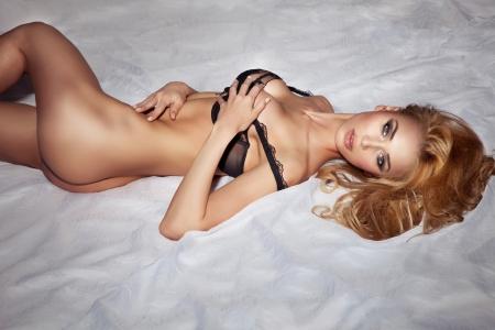 sexy girl nue: Photo sexuelle femme blonde couch�e nue dans son lit, d�tente, regardant la cam�ra. Corps de conditionnement physique parfait.