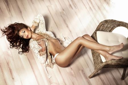 화려한 아름 다운 섹시 한 갈색 머리 여자 카메라를보고 포즈, 관능적 인 란제리를 입고 바닥에 누워. 긴 곱슬 머리. 스톡 콘텐츠