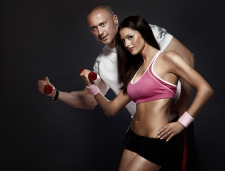 fitness trainer: Conceptual photo of very attractive couple with perfect fitness body at the gym. Beautiful woman, handsome man. Stock Photo
