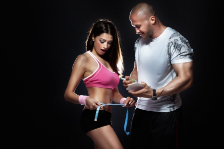measured: Photo of attractive couple at the gym. Coach measured body of beautiful brunette woman with perfect fitness shape. Stock Photo