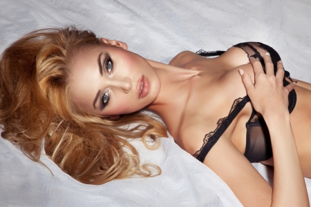 Portrait of sexual blonde woman relaxing and lying in bed wearing elegant bra, looking at camera Stock Photo