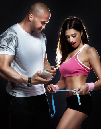 profesional: Conceptual photo of beautiful young brunette woman measuring her body with profesional trainer.