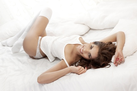 Photo of beautiful sensual young woman smiling in bed at the morning