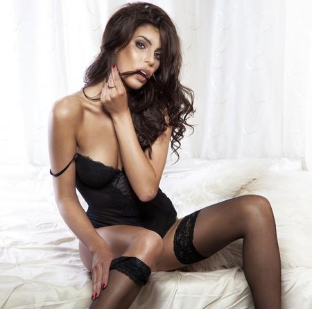 mujer desnuda sentada: Retrato de mujer sensual morena llevaba ropa interior negro sexy, posando en el dormitorio. Foto de archivo