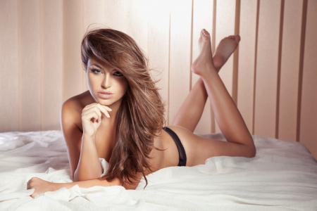Beautiful sexy woman in black lingerie lying on her stomach on bed, looking at camera. Long healthy hair. photo
