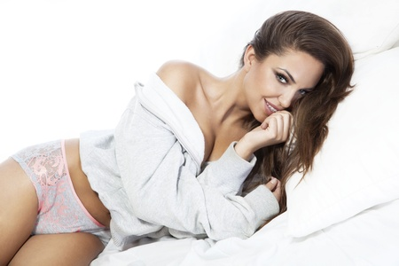 seducing: Photo of beautiful young happy woman lying on bed, relaxing, smiling and looking at camera.