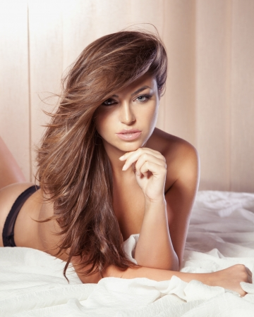 Portrait of beautiful young sensual woman lying on bed, looking at camera. photo