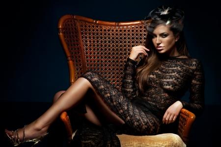 セクシーなブルネット美女ポーズ、椅子に座って、エレガントな黒のドレスを着ての写真。カメラを見てください。