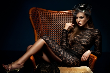 Photo of beautiful sexy brunette woman posing, sitting on chair, wearing black elegant dress. Looking at camera. photo