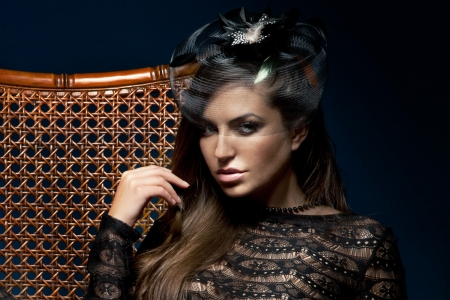 Portrait of beautiful elegant brunette woman posing in black hat, lookinga ta camera. Stock Photo - 20600440