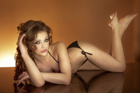 wet body: Attractive young woman relaxing, lying in black swimwear