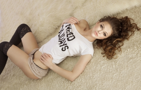 Fashionable young brunette sensual woman lying on fur photo