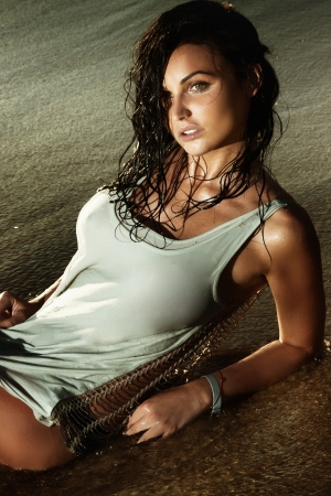 naked female: Photo of sensual brunette woman relaxing, lying on the beach.